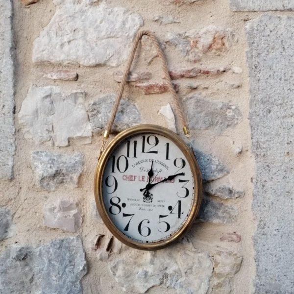 RELOJ OVALADO METAL DE PARED CON COLGADOR CUERDA Bonito reloj de metal dorado envejecido, de forma ovalada, con una cuerda para colgar en la pared. Tamaño: 26,5cm x 31cm mas 25cm de cuerda apro.